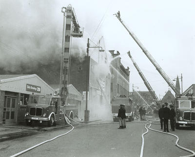 Keywords: cash and carry warehouses, disasters, fire appliances, fire engines, fire fighters, firemen, fires, Glasgow Fire Brigade, hydraulic lifts, Kilbirnie Street Fire, policemen, scooshers, Sher Brothers, turntable ladders
